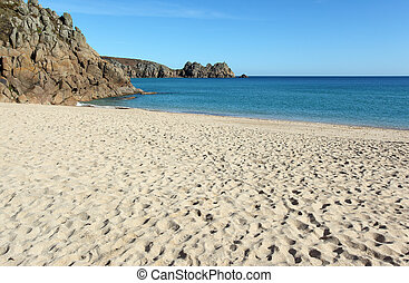 Porthcurno sandy beach and Logan rock in Cornwall UK