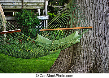 Place To Retire - Green hammock in a summer backyard