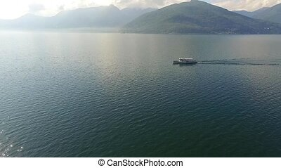 Turistic boat on lake with mountains aerial shot beauty view