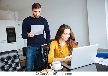 Couple paying their bills online with laptop at home
