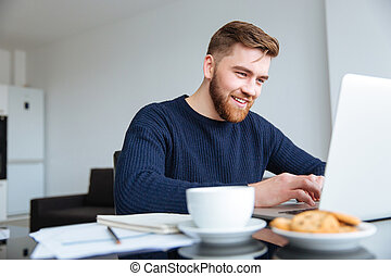Smiling man using laptop computer at home - Portrait of a...