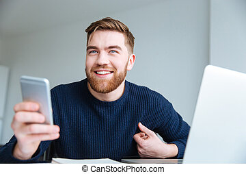 Man holding smartphone at home - Smiling young man holding...