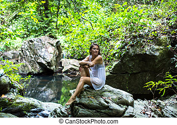 woman sitting near the forest pond - Young attractive woman...