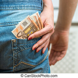 Woman taking money out of mans pocket