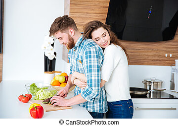 Tender woman hugging her husband while he cutting vegetables...