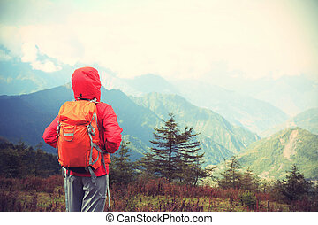 young determined woman backpacker hiking on mountain peak