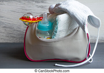 Women's handbag with items to care for the child: bottle of...