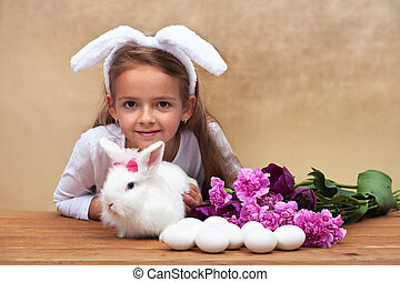 Happy little girl with her spring rabbit and seasonal...