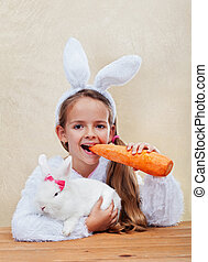 Happy easter costume girl holding her bunny and a large...