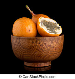 Passion fruit maracuja granadilla on wooden bowl, black...