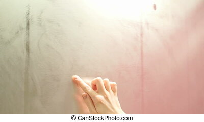 the girl draws a finger drawing a heart on a foggy mirror fast