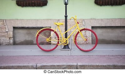 Bright bicycle parked at the lamp post, people cross the...