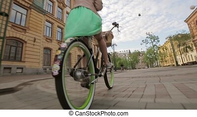 Back side of girl in a dress on a bicycle, wheels focus in in summer evening.