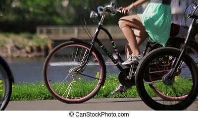 Girl in a dress on a bicycle among people, wheels focus in in summer evening.