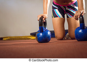 Fitness woman doing push ups with kettlebells - Crossfit...