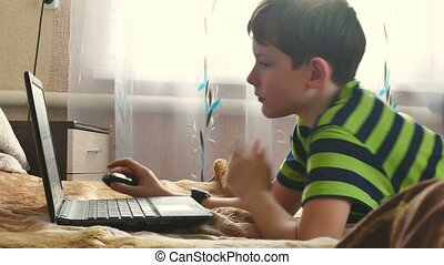 boy is playing laptop browsing the Internet - boy is playing...
