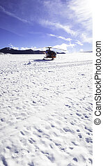 Helicopter skiing - helicopter transporting skiers