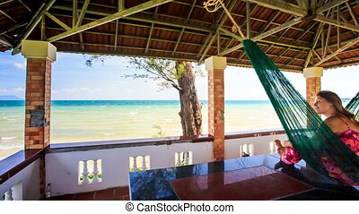 Camera Moves by Girl in Hammock through Pavilion to Sea -...