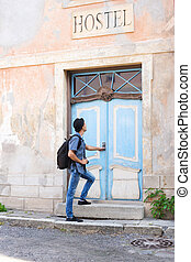 Handsome male tourist entering an old building (hostel,...