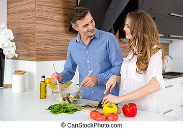 Happy couple cutting vegetables and making salad on the...