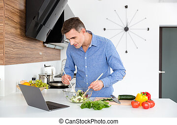 Attractive male looking on screen of laptop and cooking -...