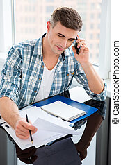 Confident man sitting with bills and talking on cell phone