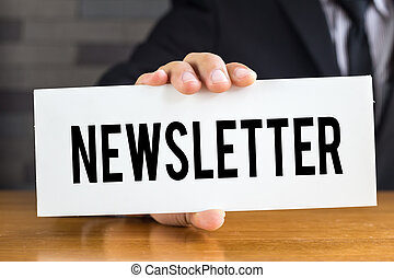 Newsletter, message on white card and hold by