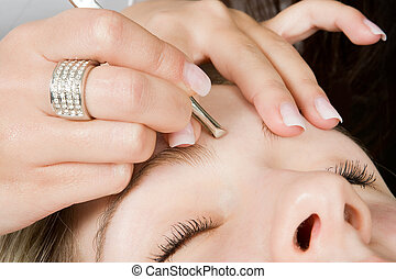 Eyebrow treatment - Beautician depilating a woman\'s...