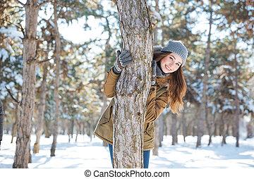 Smiling woman walking in winter park