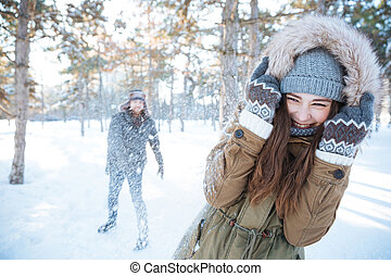 Happy young couple playing snowballs outdoors - Happy young...