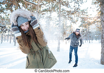 Beautiful happy couple throwing snowballs and having fun in...
