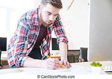 Concentrated handsome man working and drawing blueprint -...