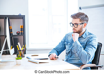 Thoughtful designer using graphic tablet and computer -...
