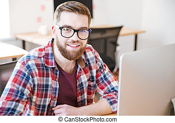 Happy handsome young man sitting and working with computer -...