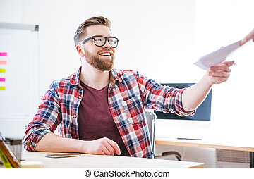 Cheerful man siting on workplace and receiving documents -...
