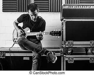 Playing his guitar backstage - Photo of a man sitting...
