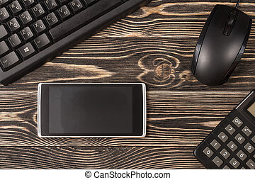 Miscellaneous office gadgets on wooden background, directly...