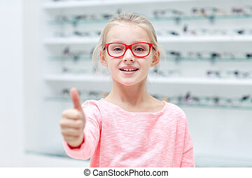 girl in glasses at optics store showing thumbs up - health...