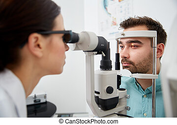 optician with tonometer and patient at eye clinic - health...
