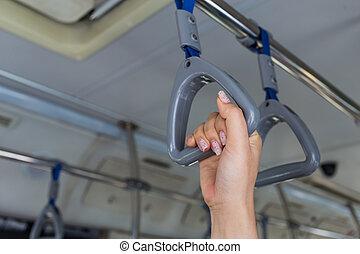 Women hand handle loop in the subway