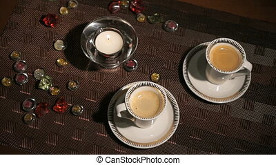 Burning the candle scattered gemstones. Two cups of beautiful aromatic coffee
