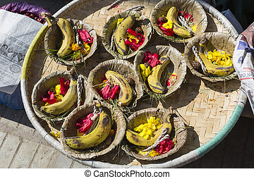 Bowls with saffron water and flowers at Bodhnath stupa in...
