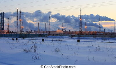Refinery at sunset sky background Frosty snowy winter...