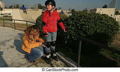 Young skater boy ready to ride - Mother dressing her son...