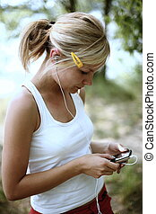 Portrait of a teenager wearing headphones and listening to music on her mp3 player
