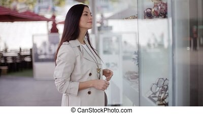 Young woman shopping in an urban mall standing looking at...