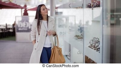 Stylish young woman browsing in a shopping mall looking at...