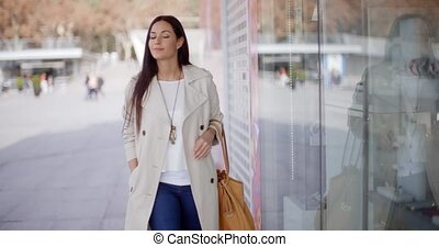 Smiling stylish woman walking past a shop window with a...