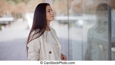 Young woman eyeing an item for sale displayed in a shop...