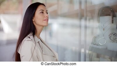 Thoughtful young woman eyeing shop merchandise as she stands...